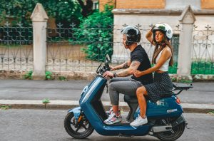 Man and woman riding blue NIU scooter