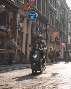 Un hombre conduciendo un scooter NIU por las calles de su barrio