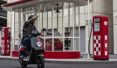 Elektrische scooter rijder zwaait naar het benzinestation