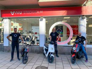 Personeel staat buiten bij de NIU Flagship Stockholm met hun scooters