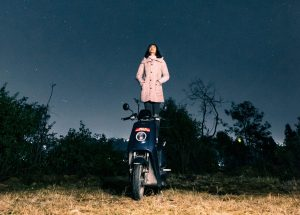 Frau steht auf einem NIU-Roller und schaut in die Sterne