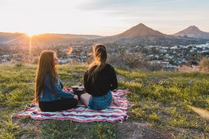 Two women outside at the park on a blanket