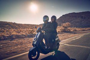 Dos riders de scooter eléctrico en el desierto
