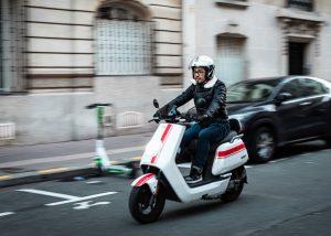 An electric scooter rider cruising through an urban environment