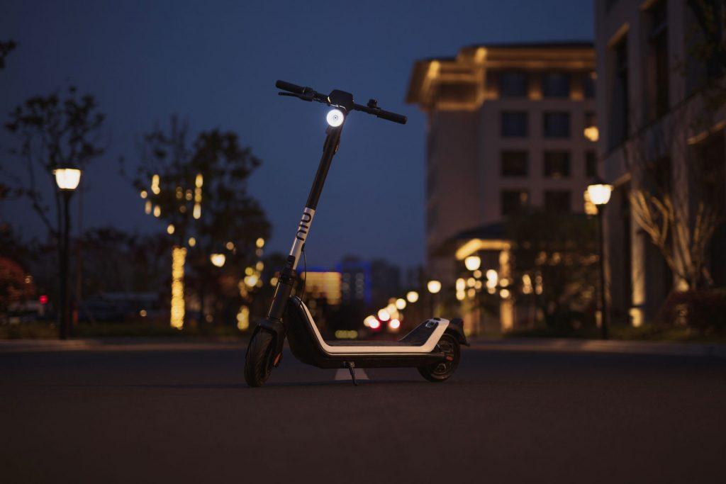 NIU kick scooter at night with street lights