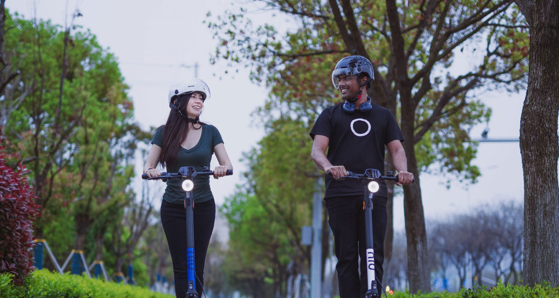 Two people enjoy riding their kick scooters through the park