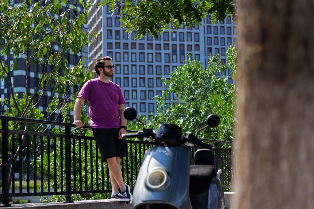 Homme avec un scooter NIU au premier plan et un bâtiment en arrière-plan Bryce près des buissons