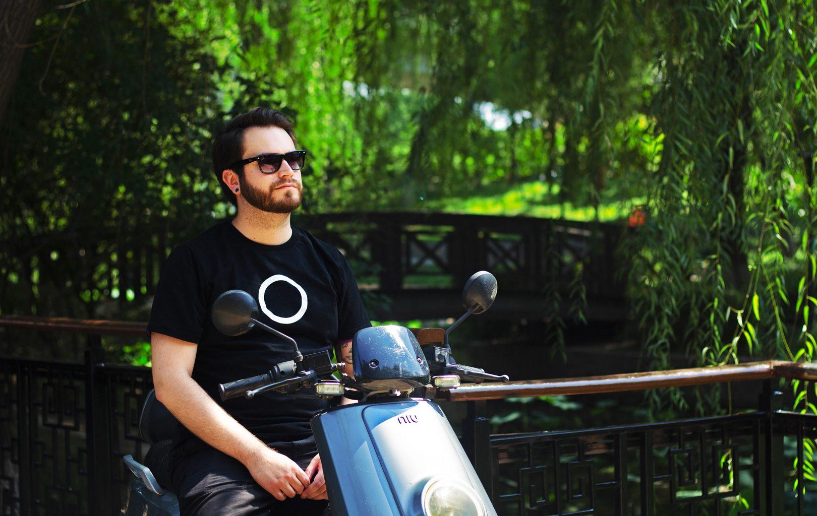 Man on a NIU electric scooter next to bridge