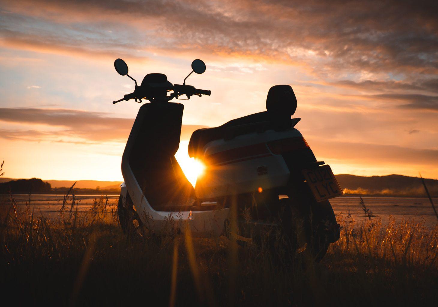 Elektrische NIU scooter met een zonsondergang en een wolk achtergrond