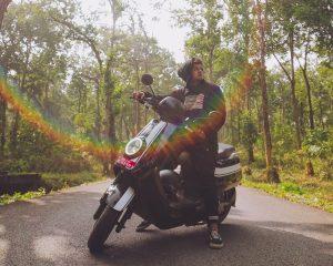 Man rijdt een elektrische scooter op een bosweg