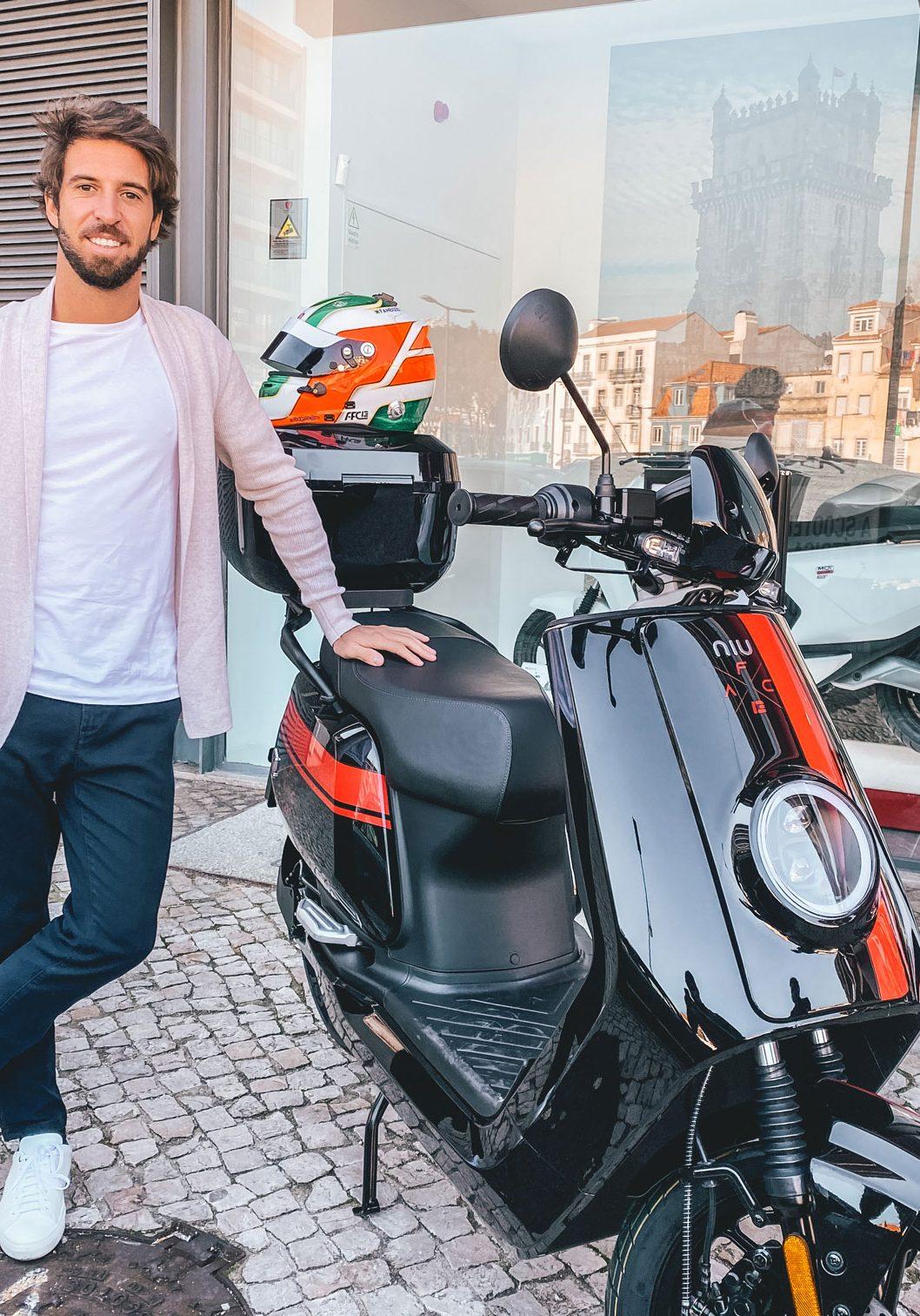 Antonio Felix da Costa stands proudly next to his NIU scooter