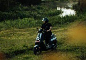 A man rides an electric scooter through a natural environment