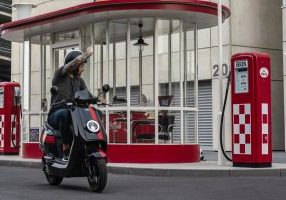 Electric scooter rider waves goodbye to the gas pump
